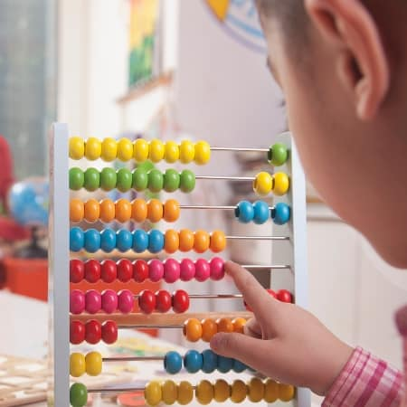 why fewer toys are better child playing with abacus