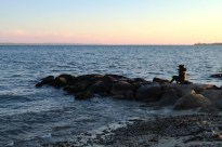 Woman eats her dinner on rocks at Falmouth Harbor