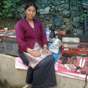 Tibetan lady selling braclets by the roadside