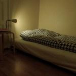 En futon med pall som sängbord och på den en sänglampa