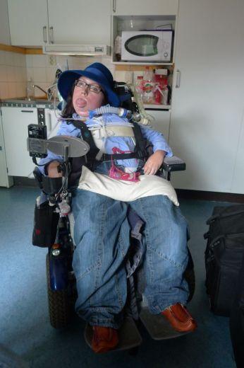 Amanda i permobil med blå hatt