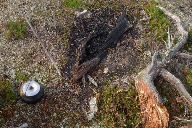 Kolnad eld med kaffepanna och makarpinne