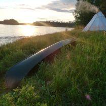 Solnedgång vid Kainuunjoki med kanot i förgrund och lavvugoattin i bakgrunden