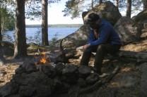 I bakgrunden ser man en sjö, på stranden några tallar och stora stenar till höger. Jag sitter vid en eld framför stenarna.