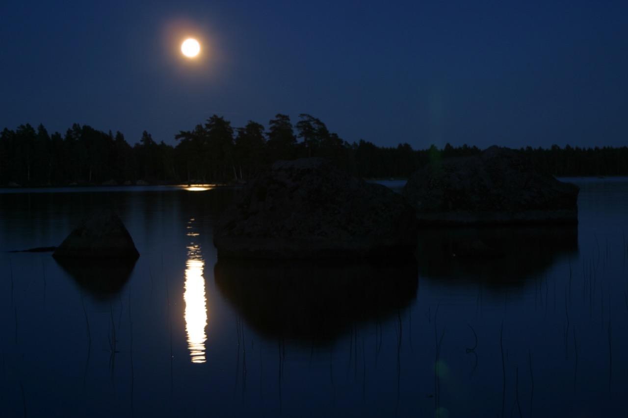 Månen som speglar sig i en sjö på kvällen