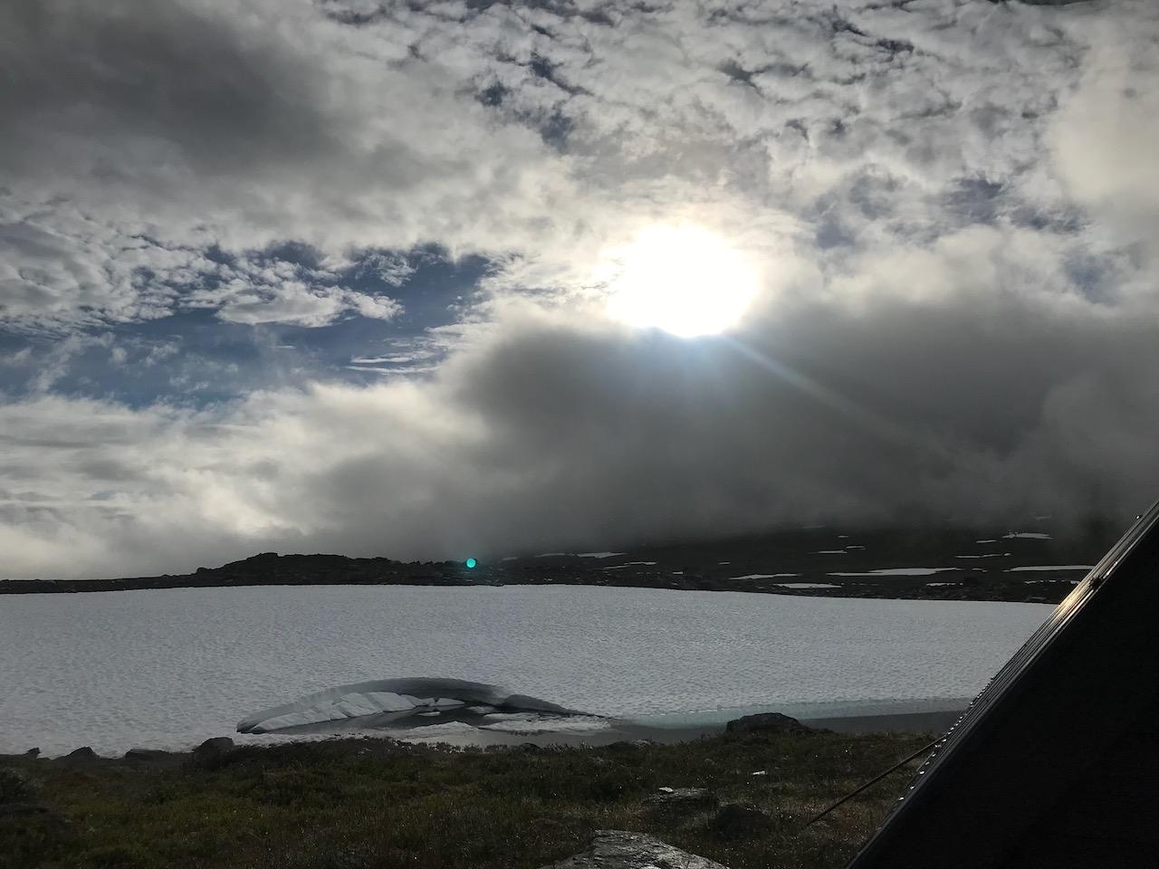 Solen går ner bakom moln i fjällen