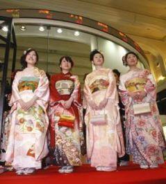 Chicas en kimono posando ante la pantalla de cotizaciones de la Bolsa de Tokio