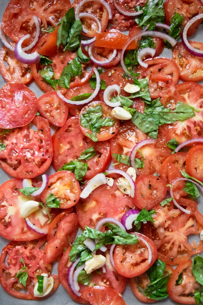 tomatoes, onions and garlic on a sheet pan