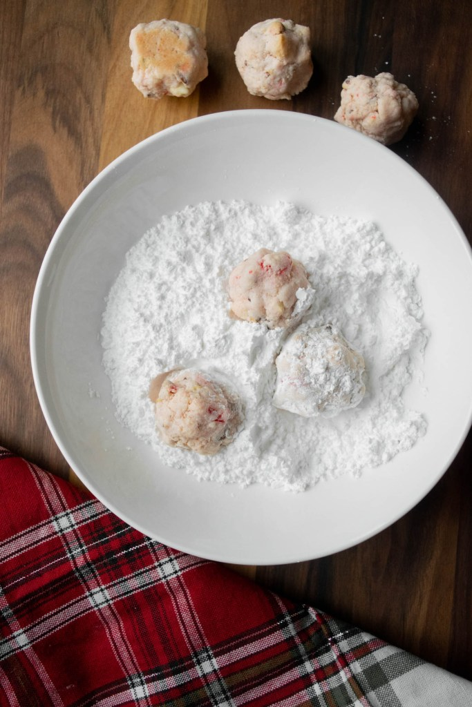 dipping the snowballs in powdered sugar