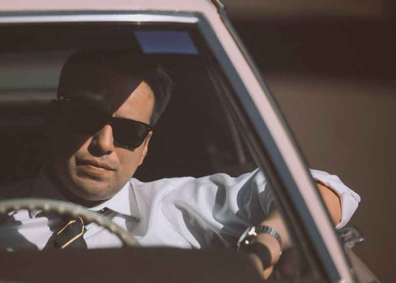 businessman in sunglasses driving retro car in town
