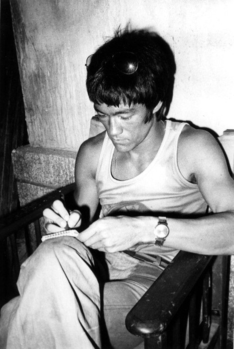 Bruce Lee writing in his Journal. Location: Unknown.