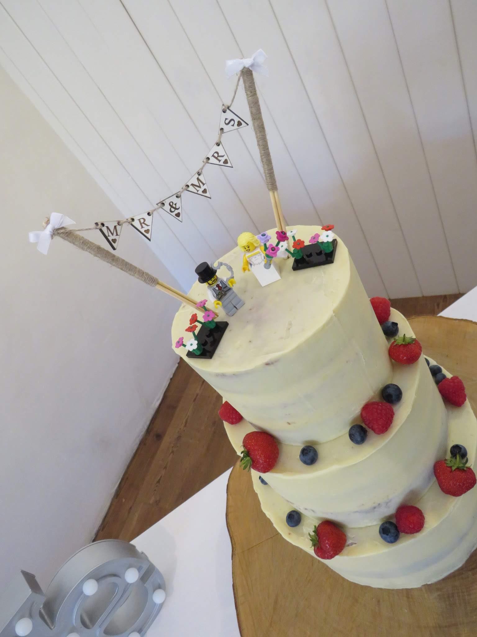 Semi-naked wedding cake with lego couple & flowers
