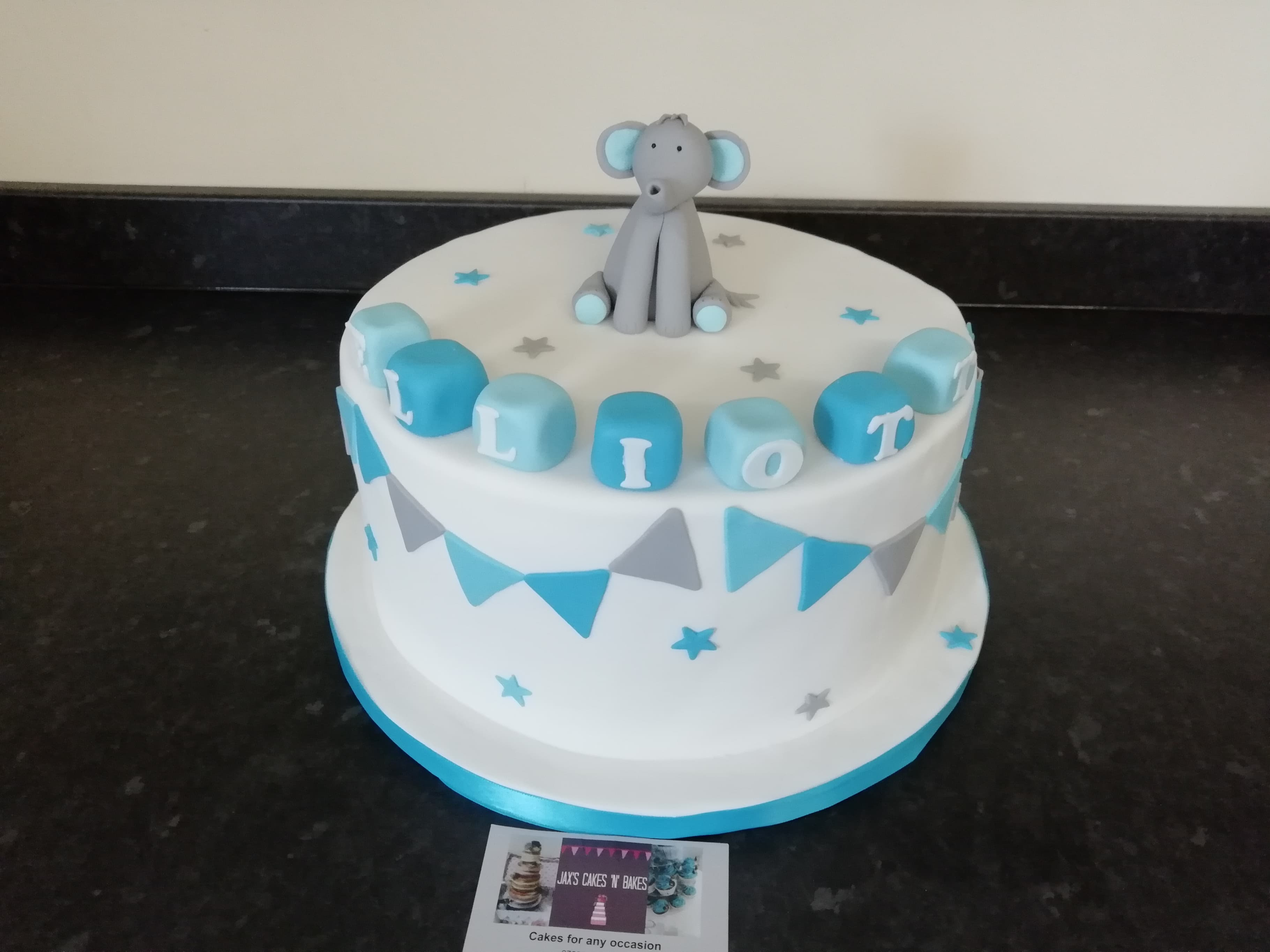 Christening cake with elephant model and bunting in blue & grey