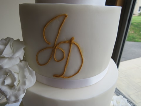 J D piped in gold on a fondant wedding cake