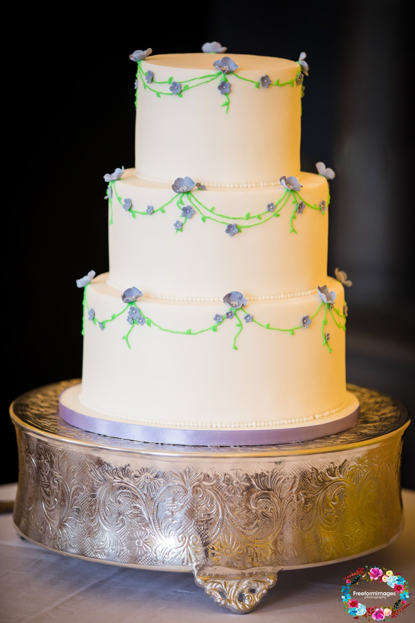 Three tier wedding cake with hand piped vines & small blue flowers
