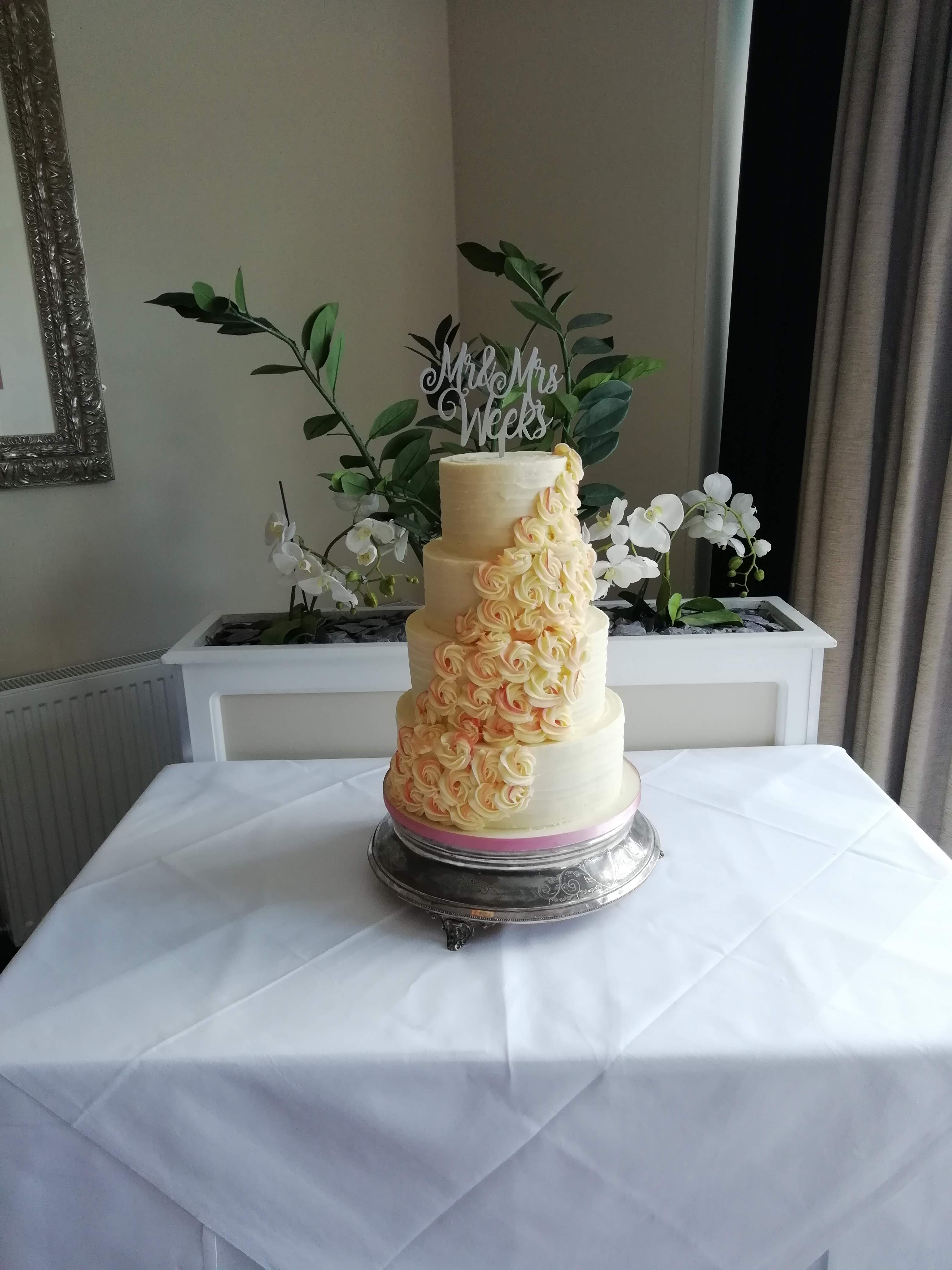 4 tier wedding cake with piped buttercream roses