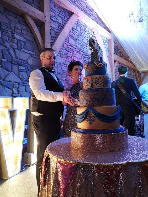 bride & groom cutting 4 tier rose gold & royal blue wedding cake
