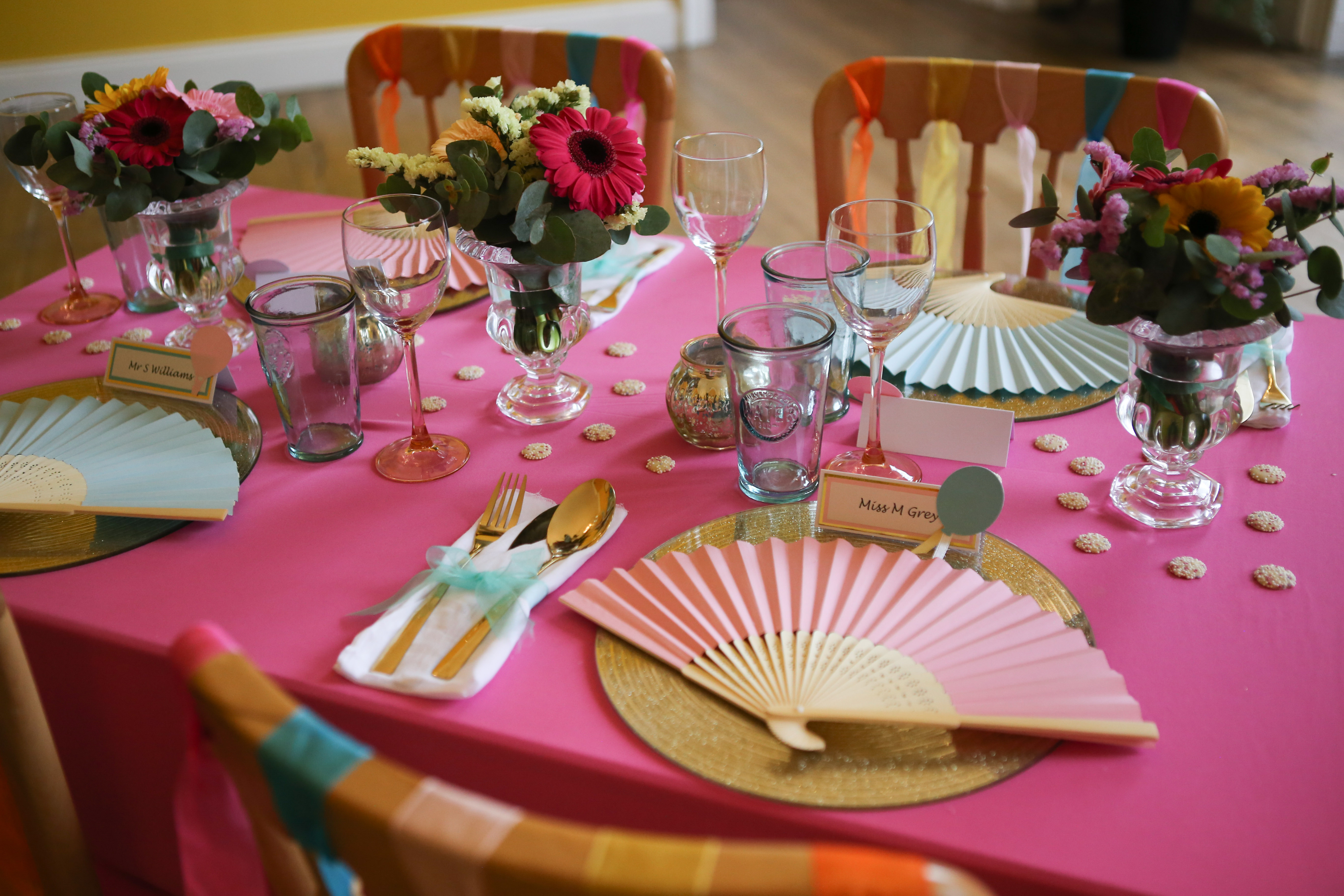 pink tablecloth with colourful fans in place settings