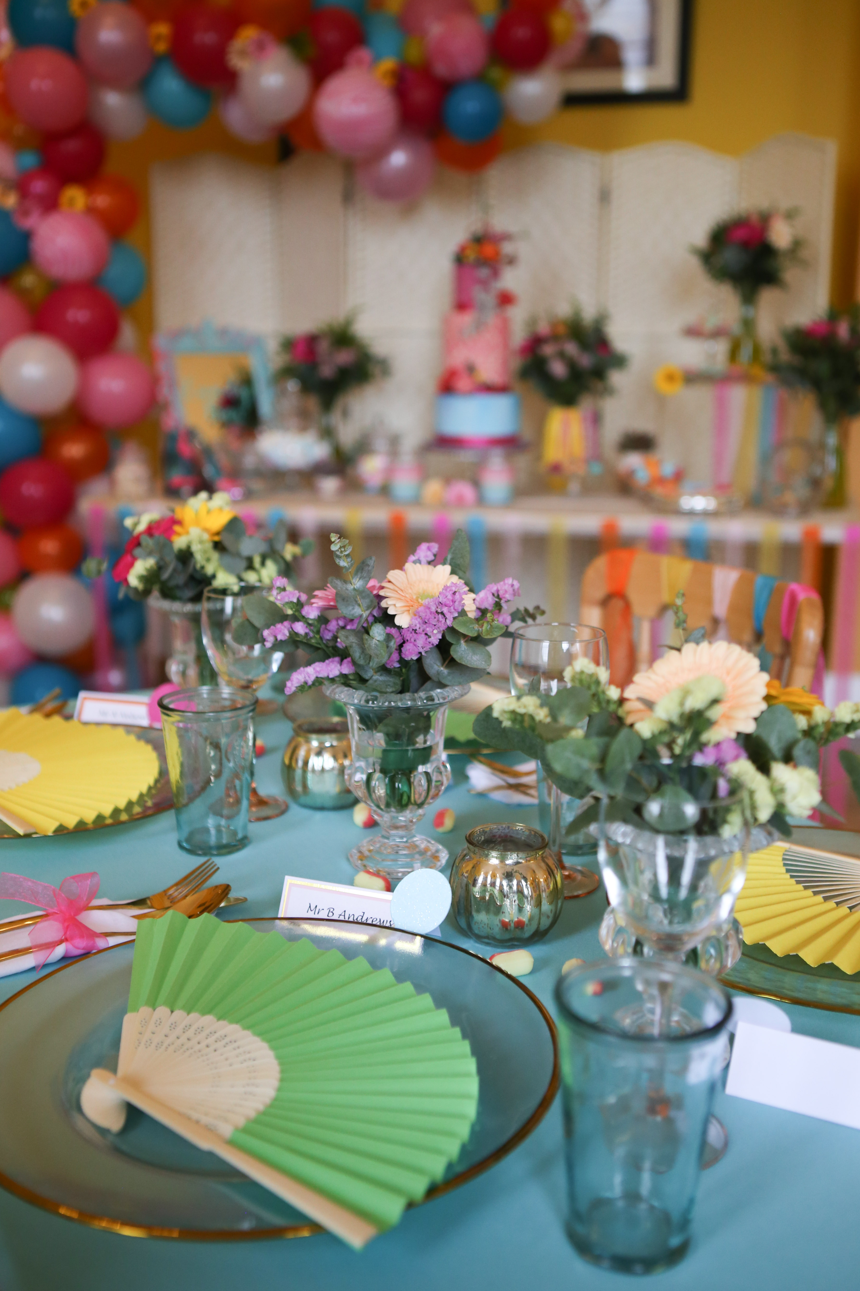Colourful wedding inspiration view of cake table in distance