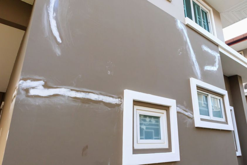 Repair crack on house wall with skim coating plaster