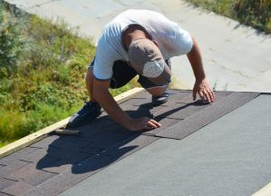 Roofer installing Asphalt Shingles on house construction roof.