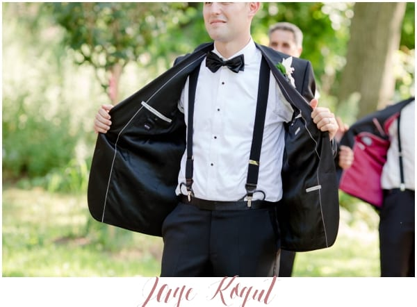 groom showing off his suspenders and tuxedo jacket
