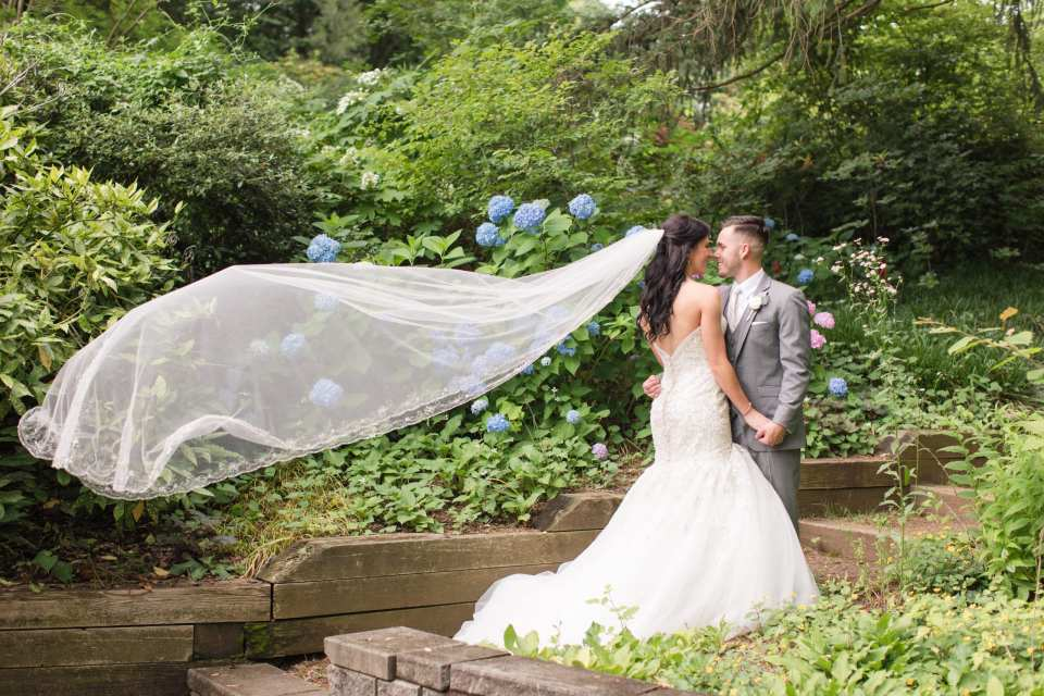 Deep Cut Gardens weddings, bride and groom wind blown veil, bride and groom garden portrait at the Gramercy at Lakeside Manor