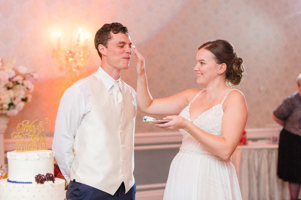 wife rubbing cake onto grooms face during cake cutting