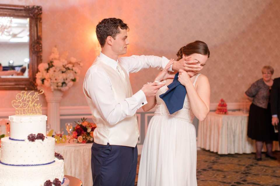groom putting cake in brides mouth and on her face during cake cutting