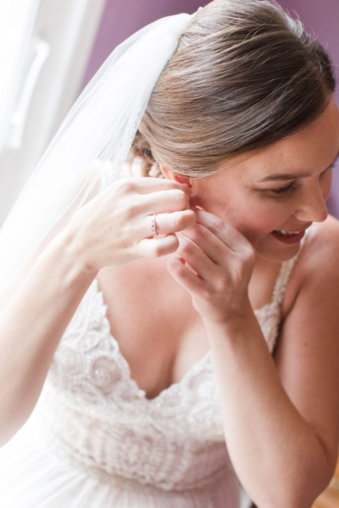 bride in veil and wedding gown putting on her earrings