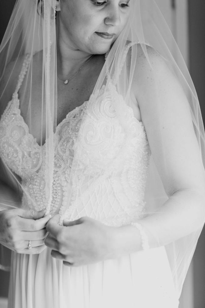 3/4 black and white shot of the bride in her gown with her veil wrapped around her, this time showing her face