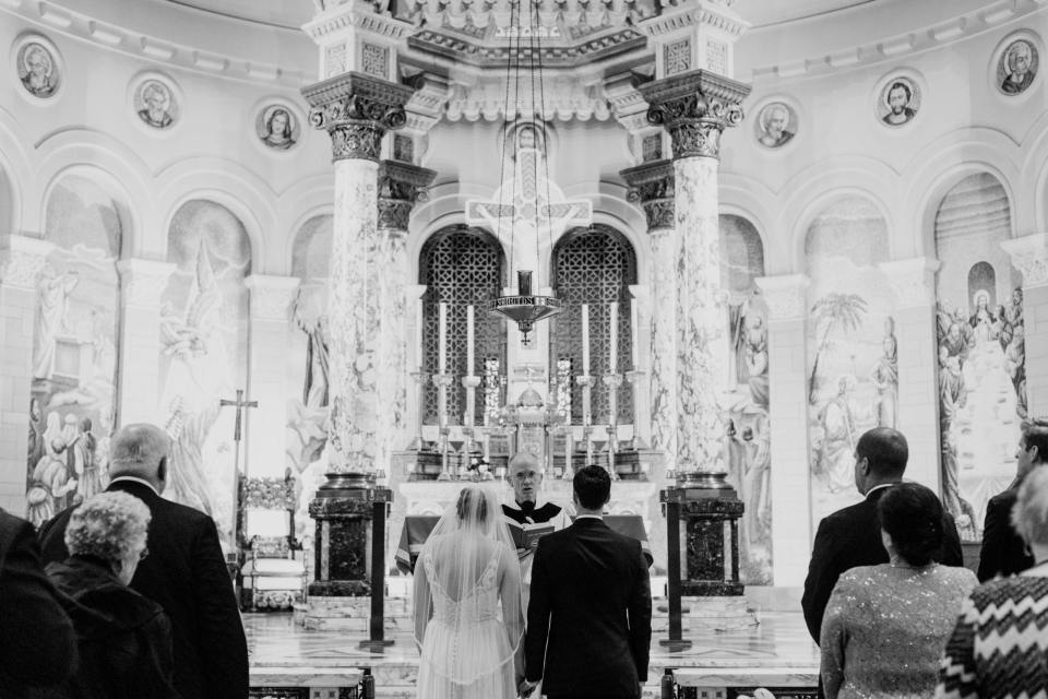 black and white photo close up of bride and groom standing before the altar