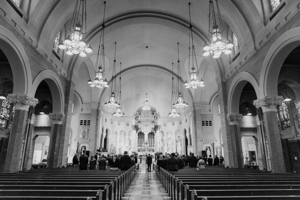 black and white wide angle photo of bride and groom standing before the altar
