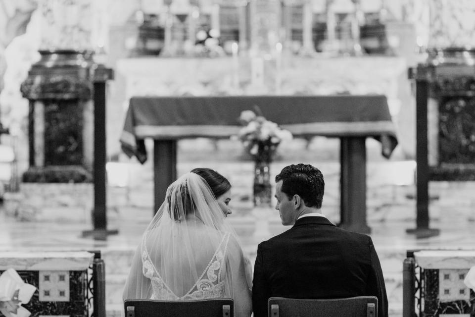 black and white photo of bride and groom sitting before the altar during ceremony, looking at each other