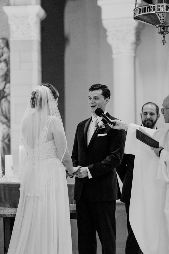 black and white photo of groom saying his vows to his bride while priest holds microphone