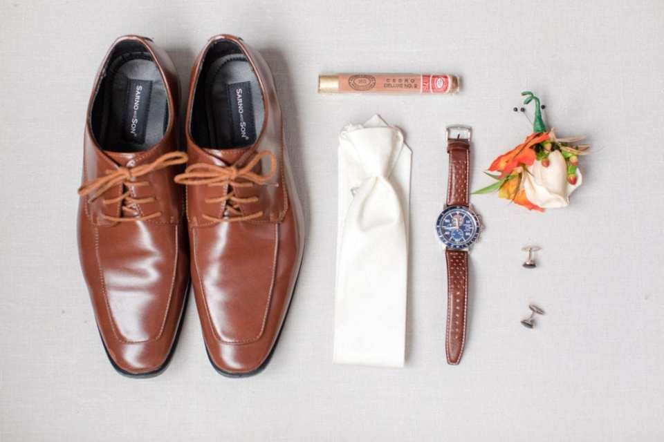 grooms accessories of brown shoes, white bow tie, brown banded watch, boutonniere, cuff links and cigar displayed on white background
