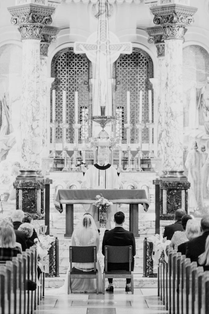 black and white photo of bride and groom sitting in front of church altar during formal church wedding service
