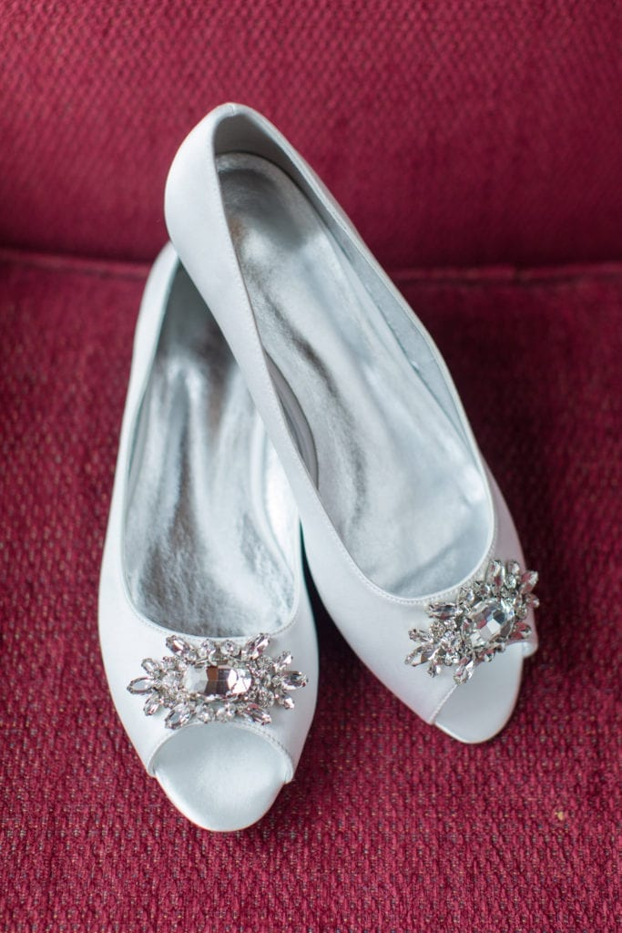 brides white flat shoes with open toe and rhinestone and crystal detail at toe opening displayed on red chair