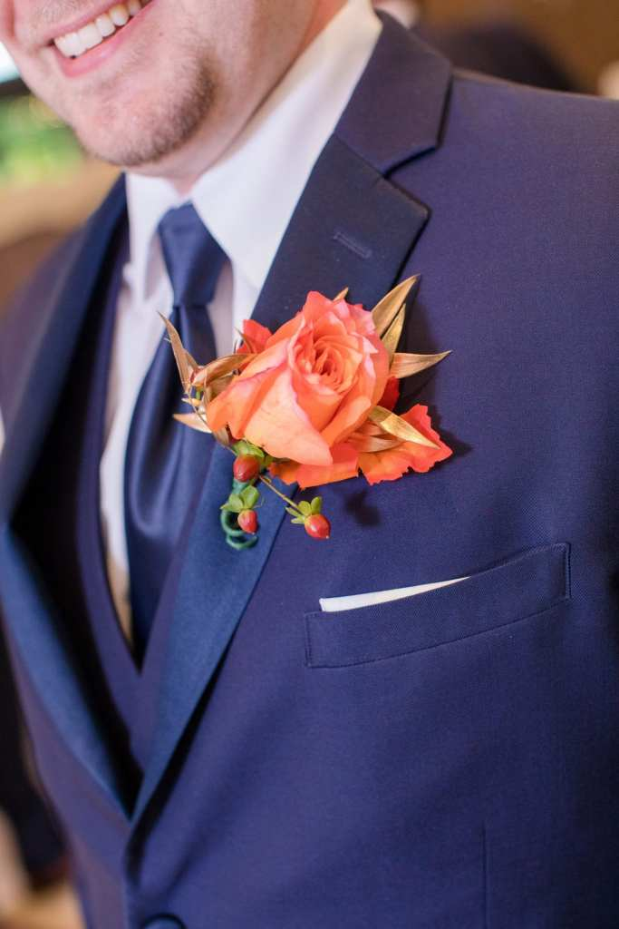 orange rose boutonniere on groomsman navy suit lapel