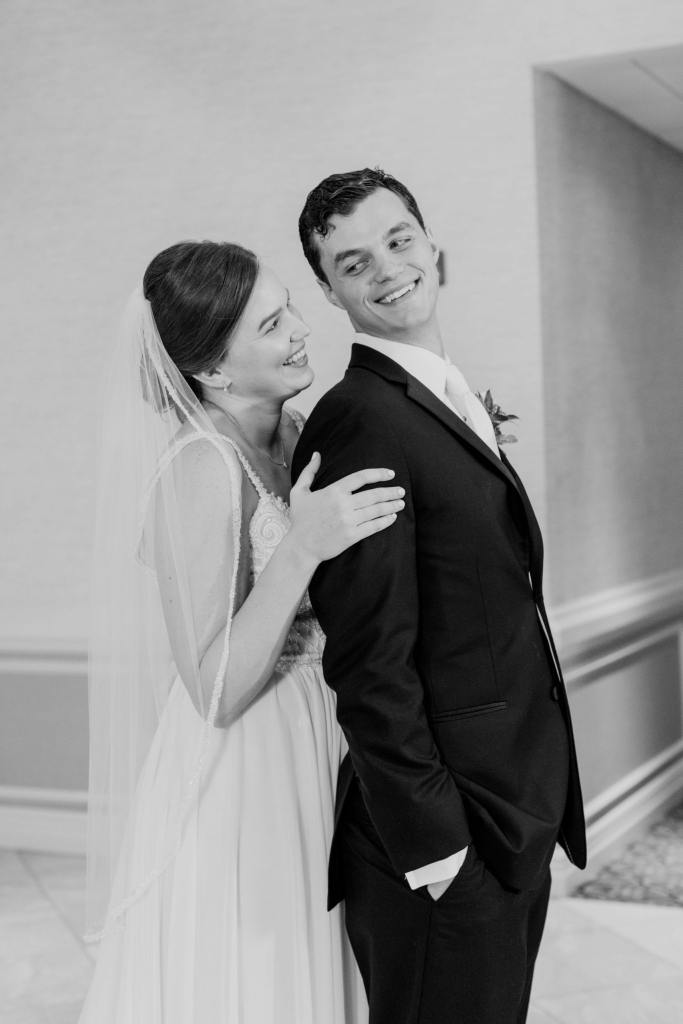 black and white photo of bride behind groom, smiling at each other