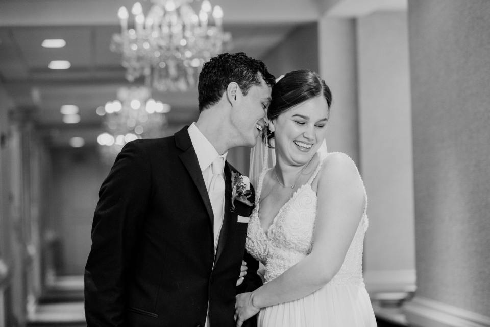 black and white close up of groom nuzzling the brides ear while in the hallway