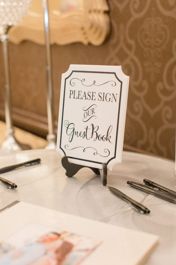 wedding signage at the entrance to the wedding reception asking guests to sign the new couples guest book