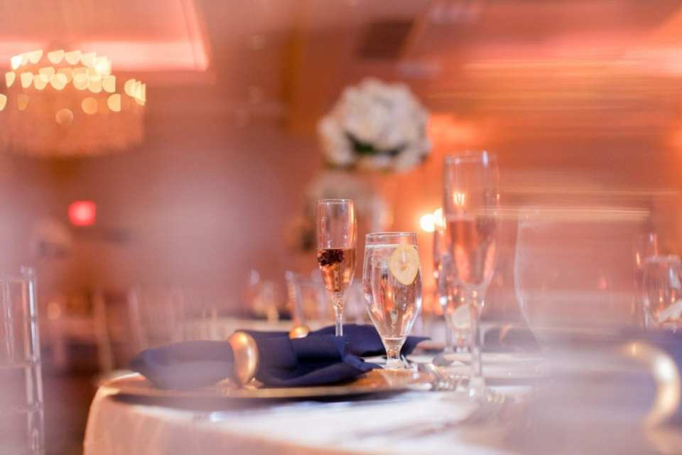 unique angle photo of place setting comprised of gold charger, navy blue napkins in gold napkin ring, and multiple bevreage glasses