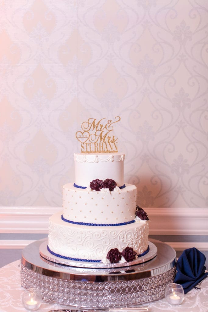 full photo of three tier white cake trimmed in navy blue frosting topped with a gold Mrs and Mrs Sturhann cake topper