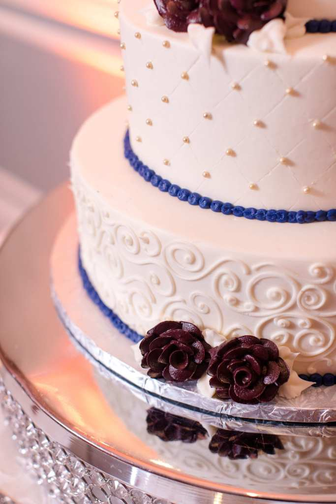 partial photo of white cake with navy blue trim and dark red flowers made from frosting. bottom tier of cake has frosting curls, next tier up has criss cross design with pearls