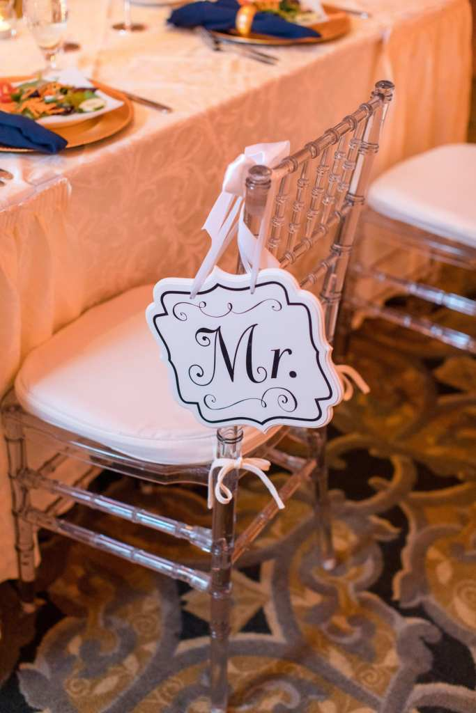 White 'Mr.' sign hanging from a lucite chivari chair
