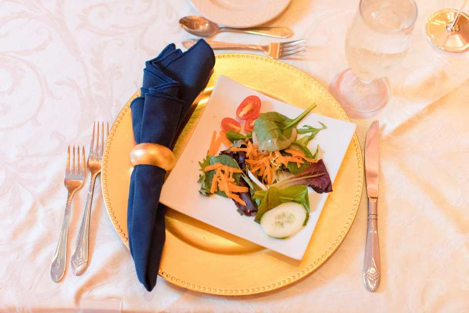 place setting consisting of a gold charger, silverware, a navy blue napkin with gold napkin ring, and a square plated garden salad