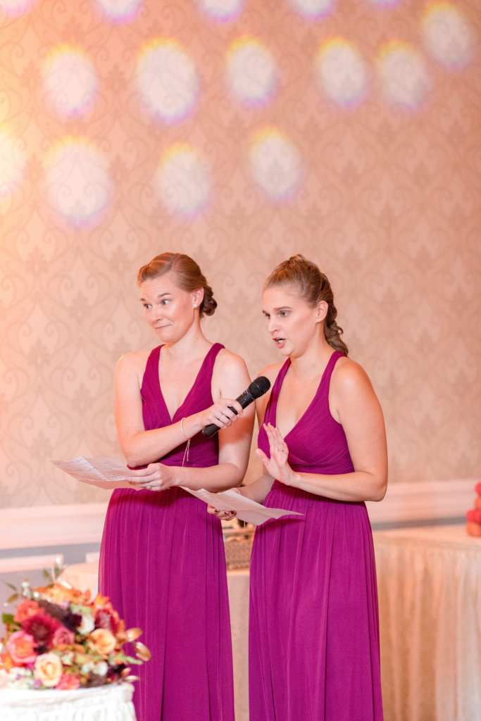 maids of honor giving speech at wedding in raspberry colored halter gowns