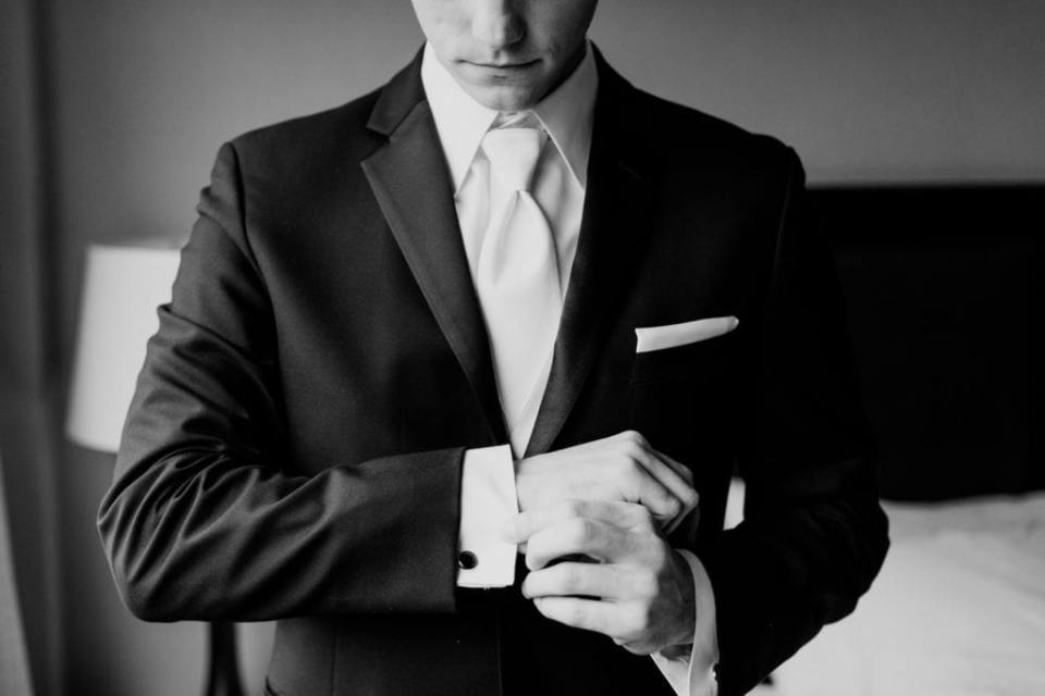 black and white photo of groom adjusting the sleeves of his tuxedo jacket