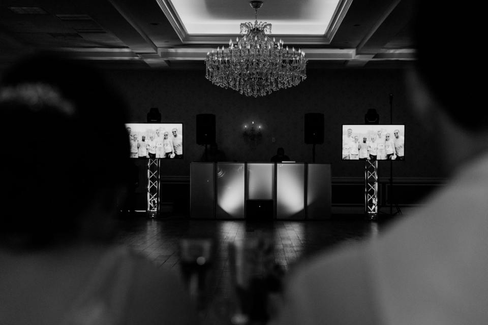 black and white photo of the dj setup with two screens on either side showing pictures. photo was shot from behind the bride and groom
